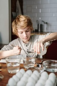 boy-in-grey-shirt-holding-clear-glass-pouring-liquid-on-3971283